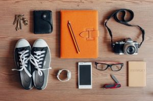 51114631 - outfit of traveler, student, teenager, young woman or guy. overhead of essentials for modern young person. different photography objects on wooden background. items include keys, camera, smart phone, glasses, passport, digital tablet, wallet, folder, watc